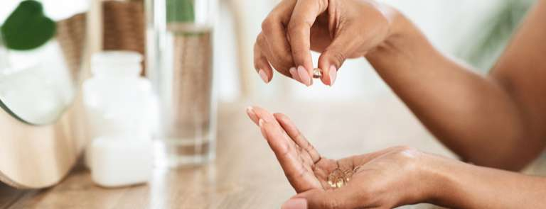 woman's hands with omega 3 supplements