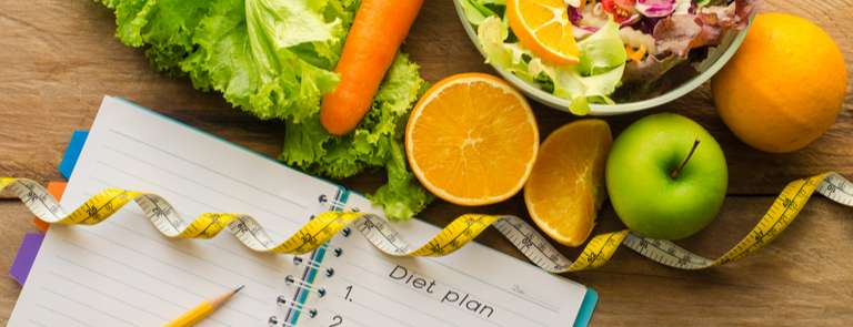 fruit and veggies with notebook and measuring tape