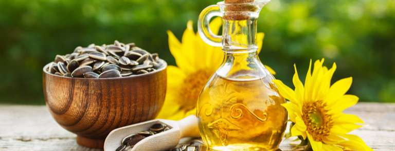 sunflower oil bottle with seeds and fresh flower