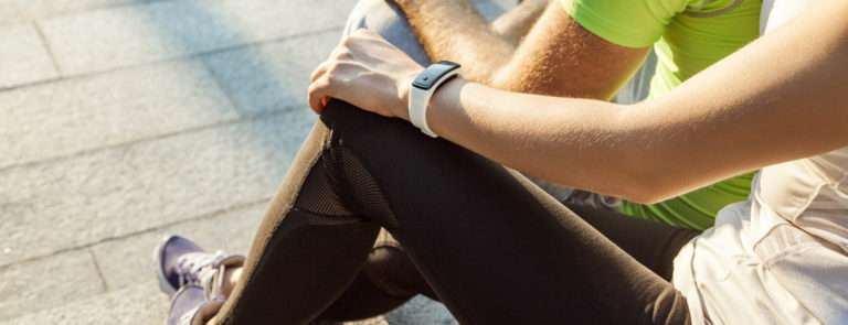 A lady and man sat down, both in sport attire, looking at their fitness watches.