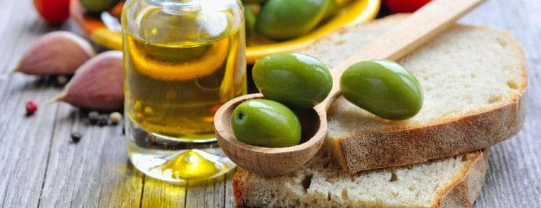 Jar of Olive Oil with bread, olives, tomatoes and garlic