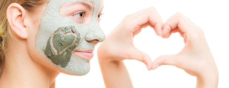 Woman in clay mud mask on face with heart on cheek isolated on white.