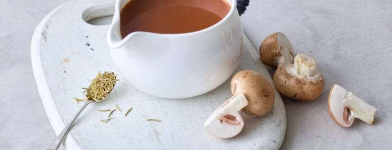 A pouring bowl containing vegan gravy with mushrooms on the side