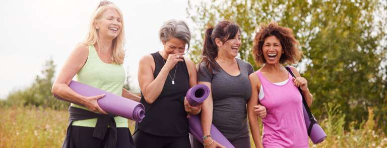 group of mature menopausal women going to a yoga class together