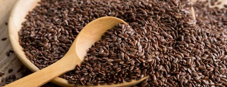 Flaxseeds in a bowl with a wooden spoon in.
