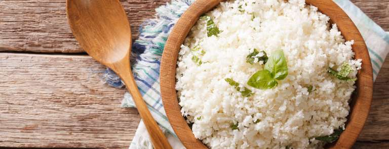 wooden bowl of fresh cauliflower rice with piece of basil