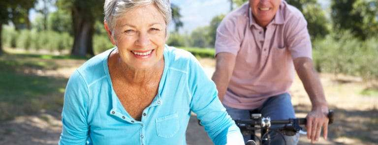 An elderly couple riding bicycles