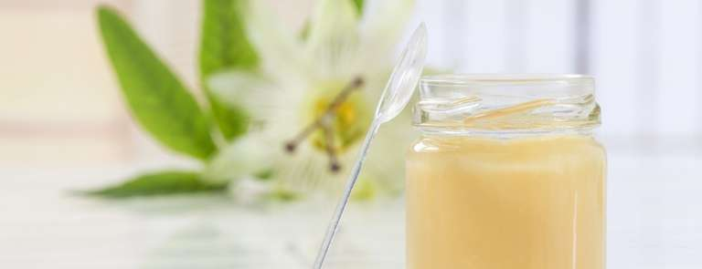 glass jar of royal jelly with flower in background