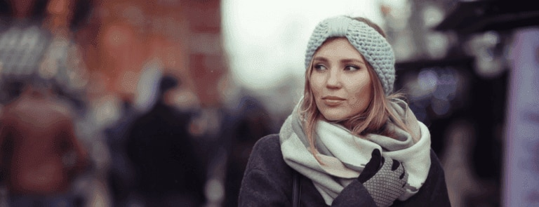 Woman wearing coat, scarf and gloves.