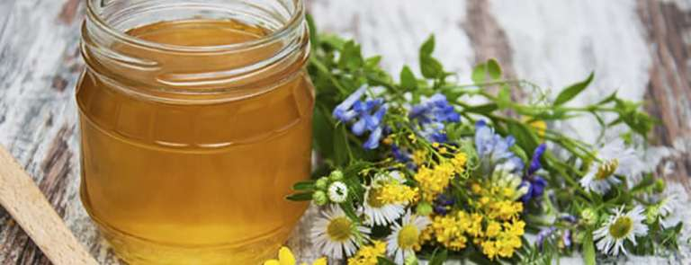 Honey and wild flowers on a old wooden background