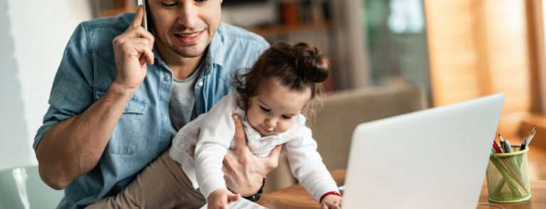 A man working from home whilst holding is baby daughter in one hand and trying to speak on the phone in the other hand.