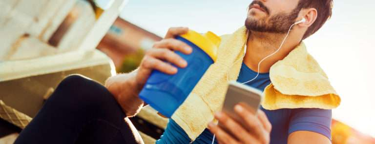 man drinking a protein shake listening to music through his phone