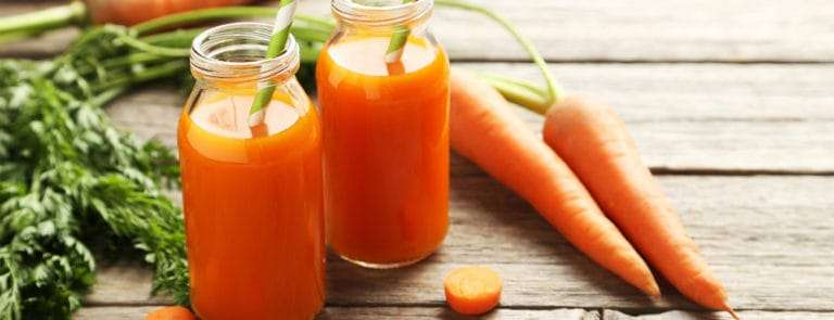 Carrot juice in bottles next to whole carrots
