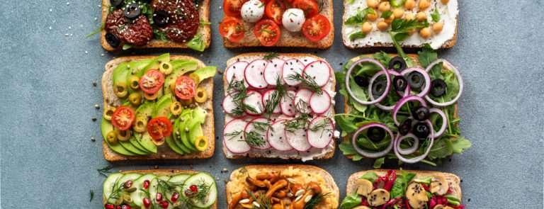 An array of 9 breads with various vegan fillings such as avocado and tomato.
