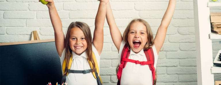 Two young girls excited to go back to school with backpacks and school uniform on