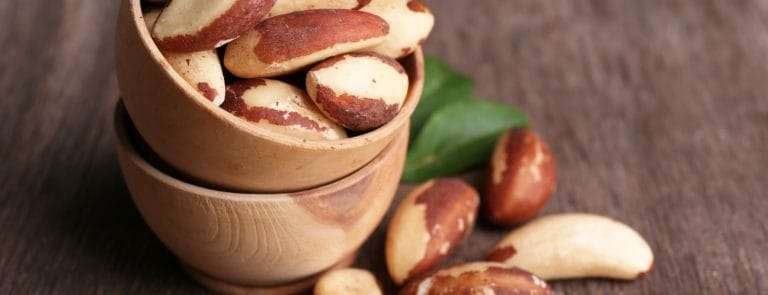 brazil nuts in a small wooden bowl stacked in another wooden bowl on a wooden table with brazil nuts scattered around