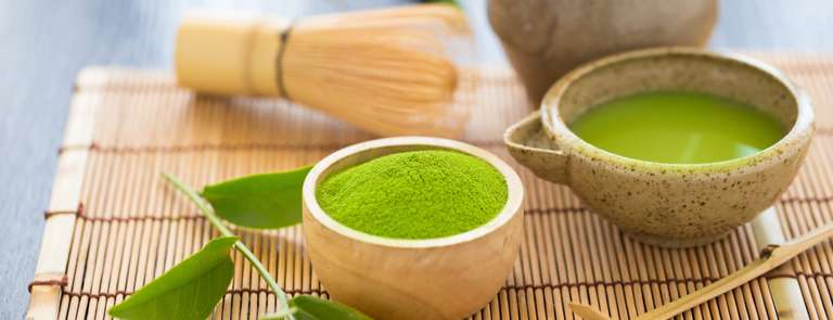 matcha green tea in teacup with powder on bamboo mat