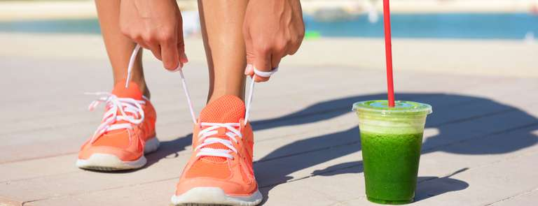woman  on juice diet running tying shoelace with cup of fresh green juice next to her