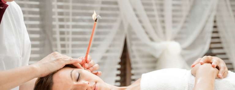 woman going through ear candling method at spa