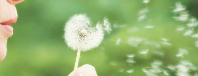 woman's mouth blowing dandelion seeds