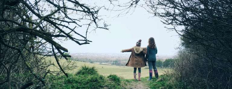 Two young children exploring in the woods wrapped up in winter coats and wellington boots