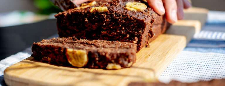 A banana bread brownie, being cut into slices on a chopping board and topped with banana slices.