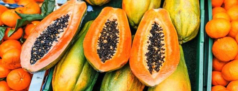 Lots of papaya in a crate, some whole and some halved exposing seeds
