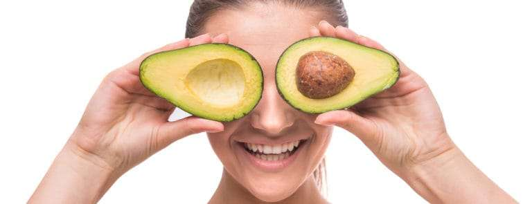 woman holding avocado in front of her eyes