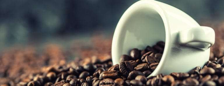 A small coffee mug holding and surrounded by coffee beans