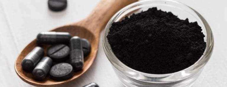 Activated charcoal tablets and powder on a wooden spoon and glass bowl