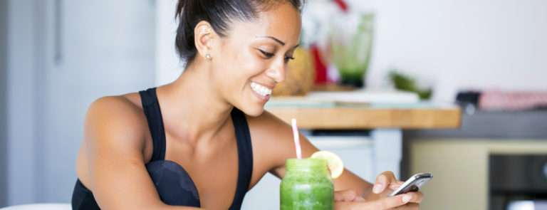 A lady sat at a table on her phone, with a fresh green smoothie in a mason jar beside her with a lemon slice in and a straw.