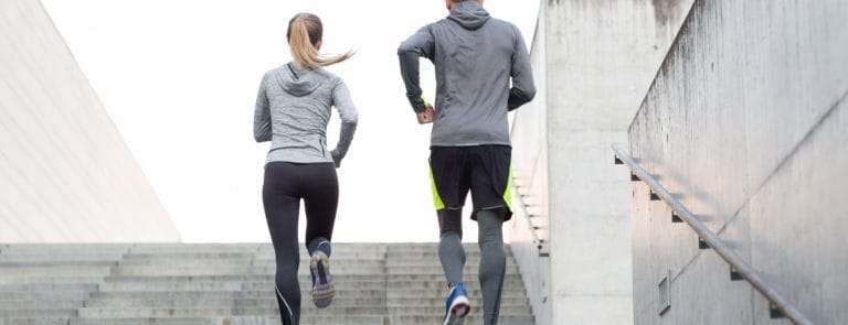 Two people running up some steps outside