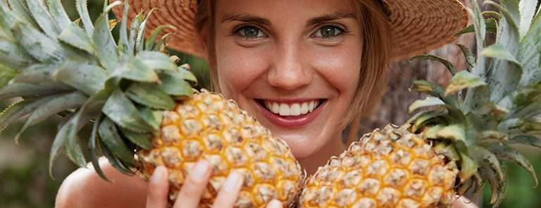 A lady wearing a sun hat holding 2 pineapples.