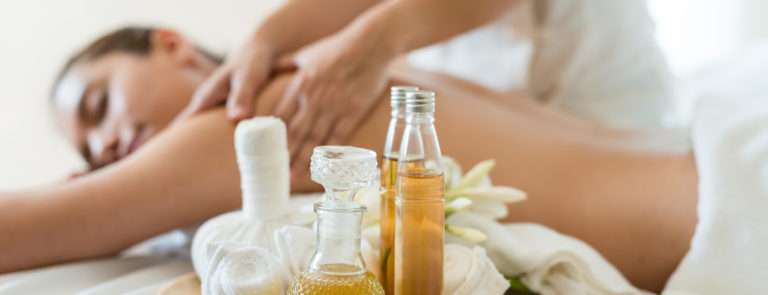 A tray with massage oils and a lady behind getting a back massage.
